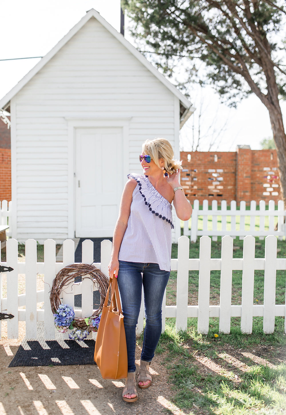 pom pom one shoulder top spring outfit by white picket fence