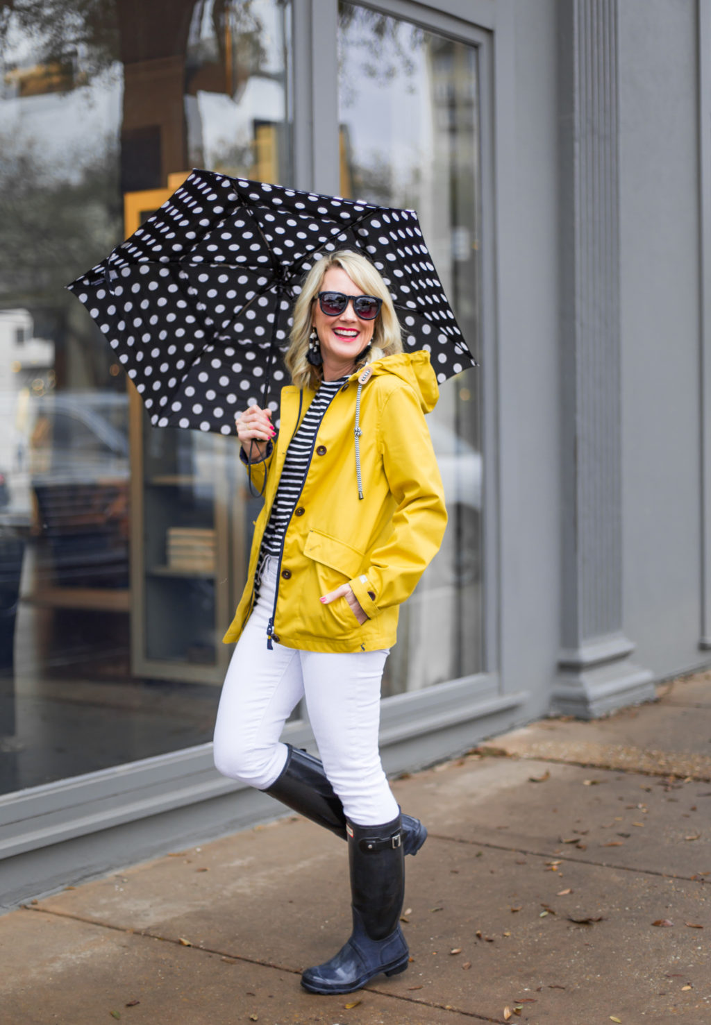 hunter boots white jeans outfit with yellow rain jacket polka dot umbrella