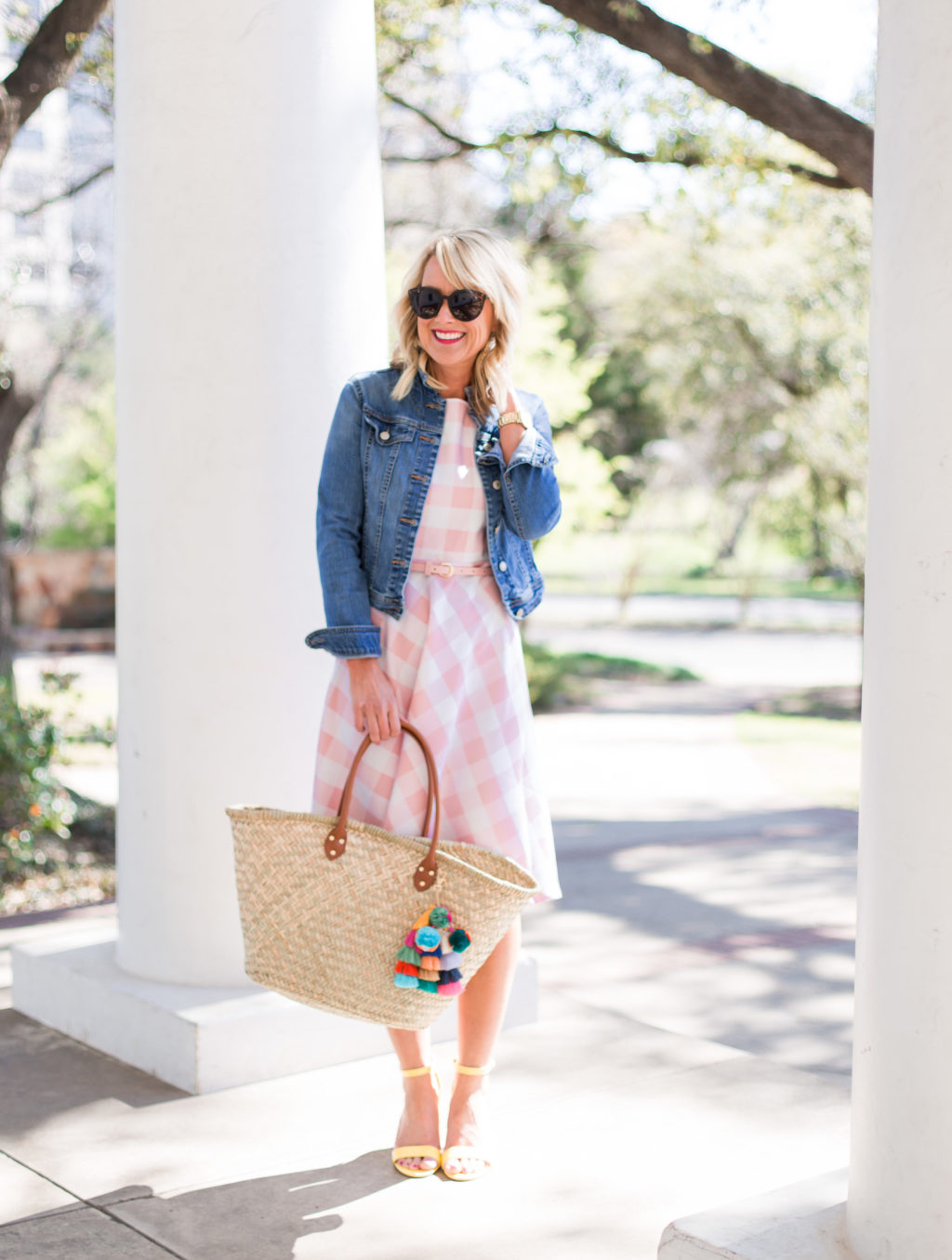woman at arlington hall dallas wearing pink gingham spring dress jean jacket and straw beach back with tassel charm