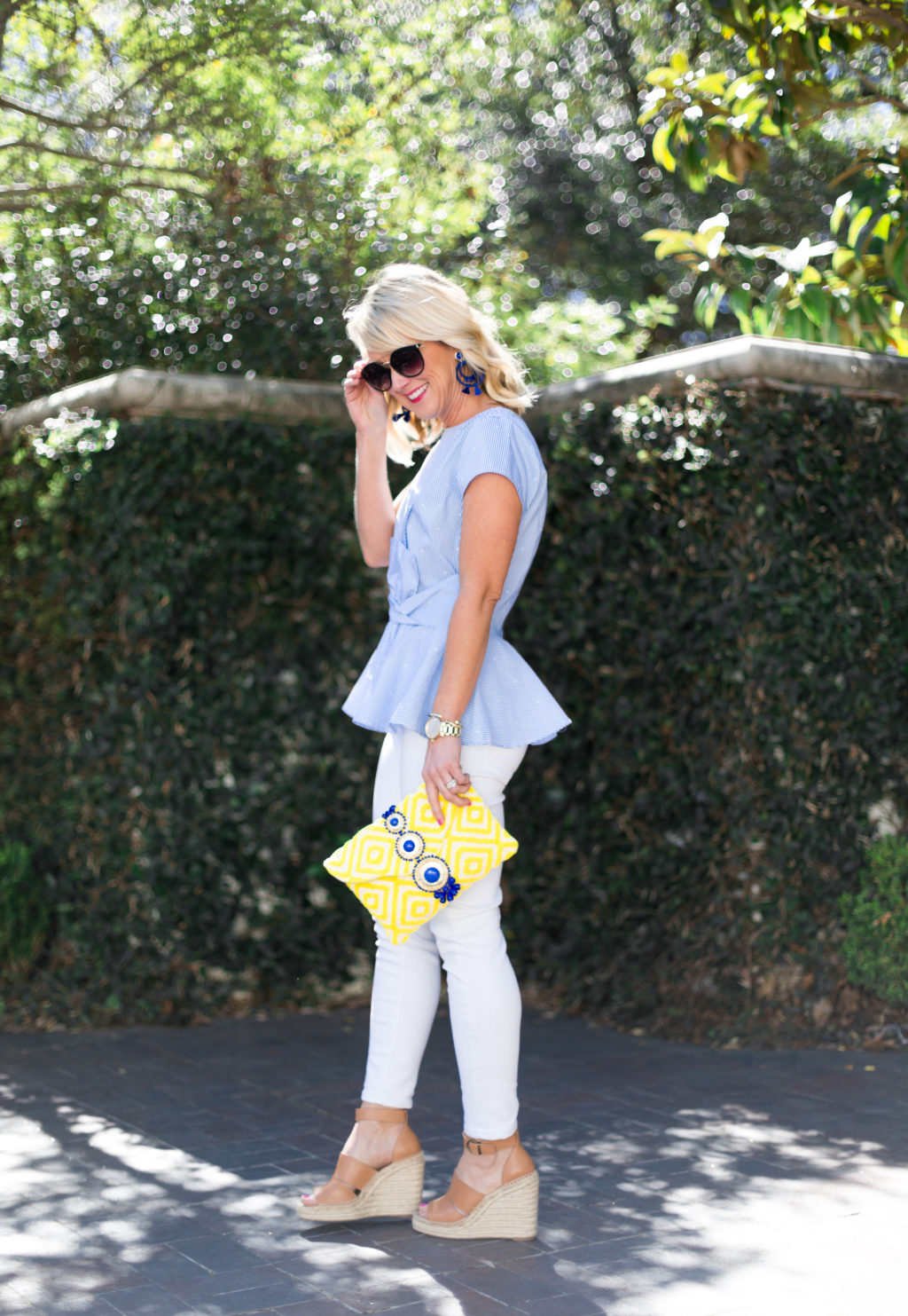 woman wearing vince camuto white jeans blue peplum top carrying steve madden yellow clutch