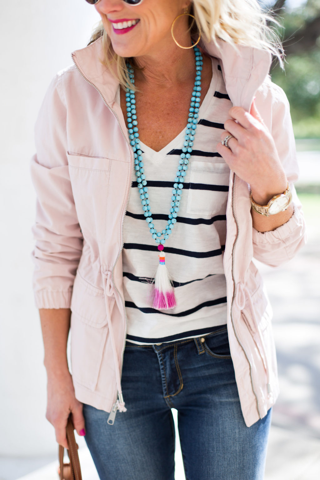 woman wearing gorjana g ring hoops pink utility jacket turquoise tassel necklace