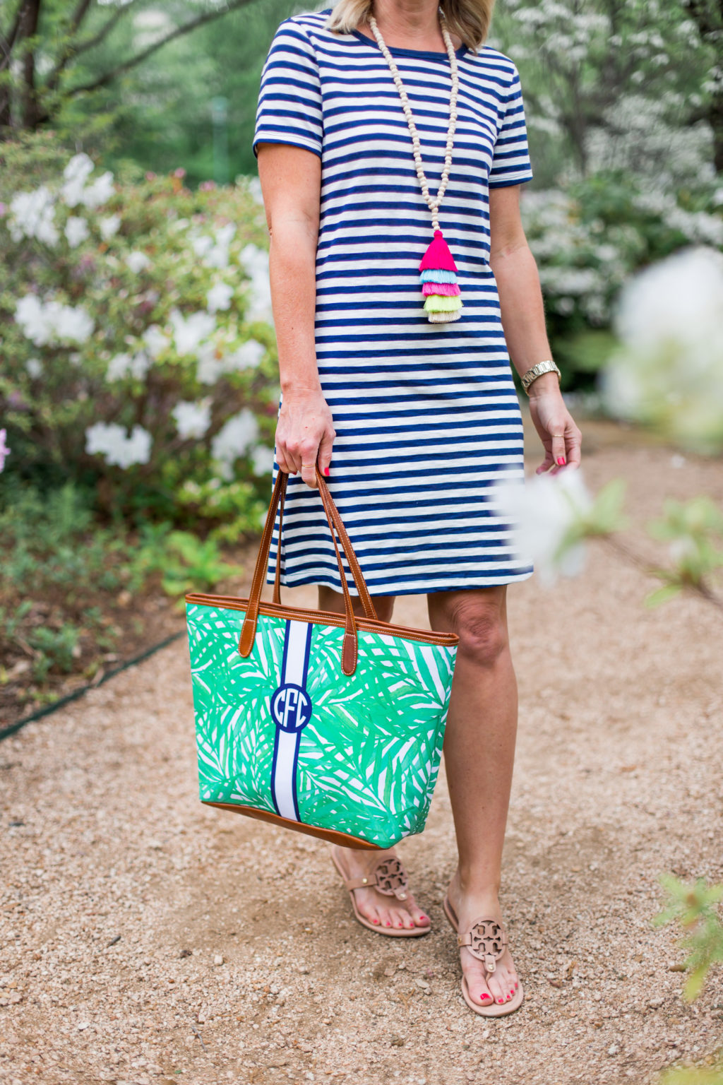 woman on oak lawn park path dallas wearing old navy striped dress and accessory concierge tassel necklace barrington tote bag
