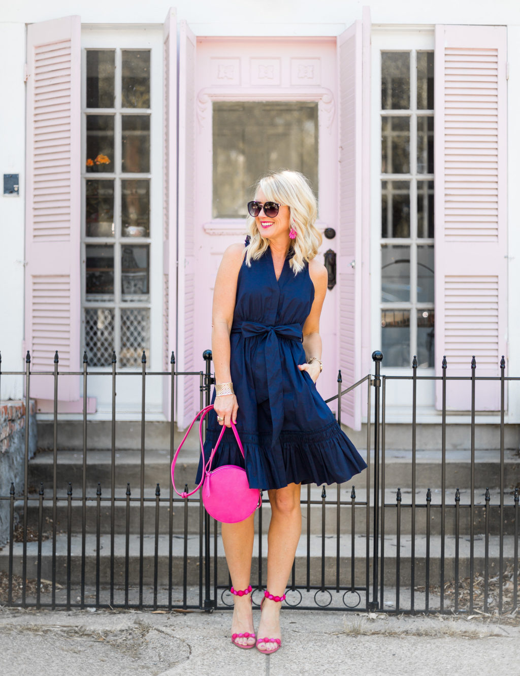 navy pleated collar shirt dress with pink circle handbag and pink heels