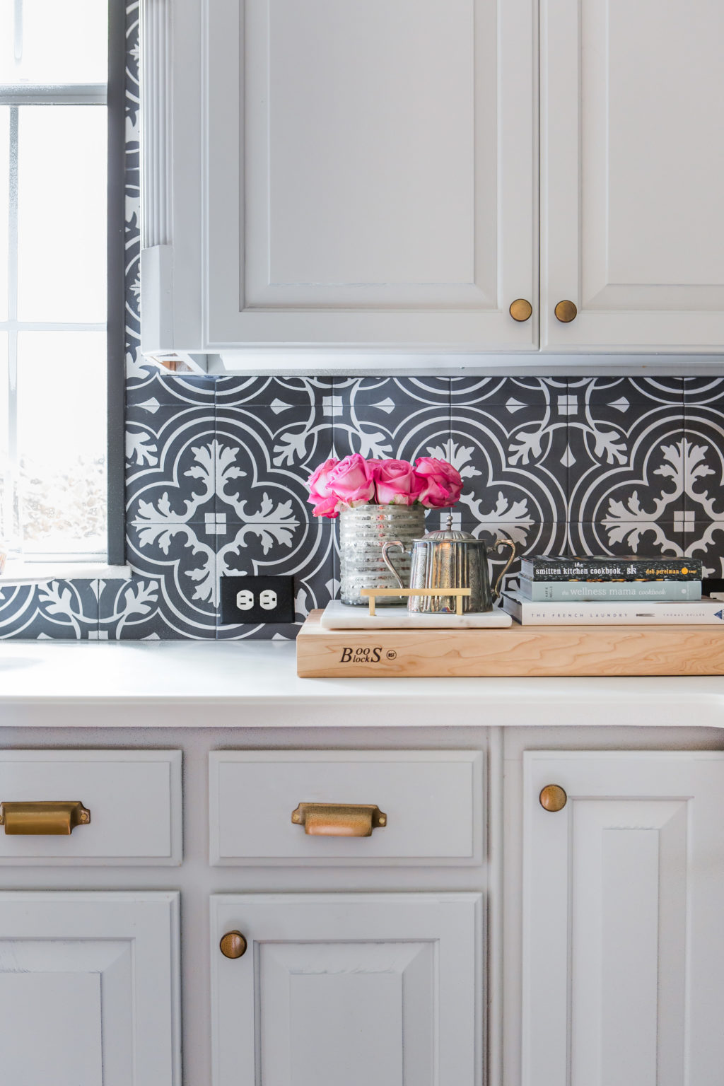 after kitchen renovation cutting board cookbooks flowers on white countertop pottery barn boulevard brass drawer pulls and knobs