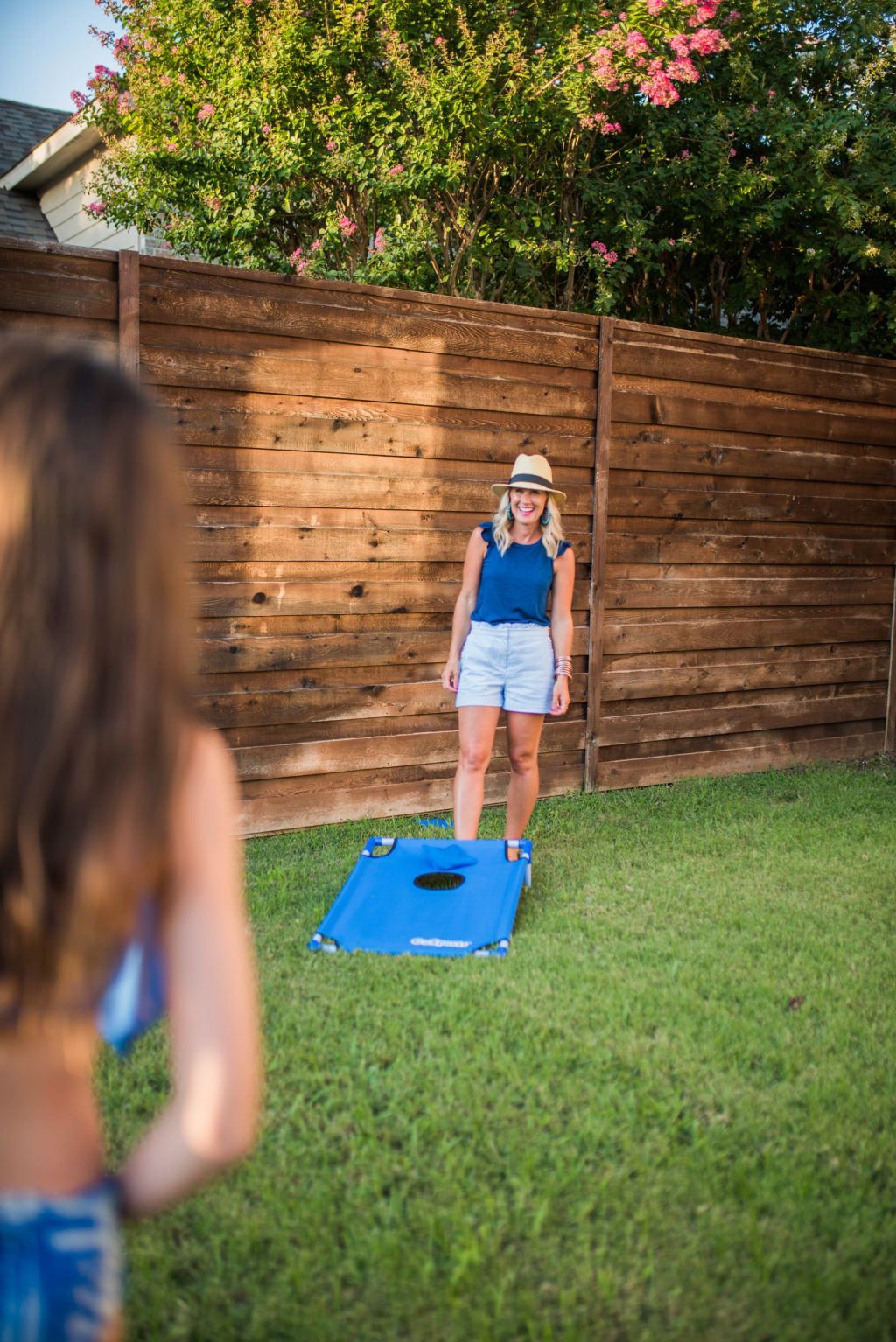 family playing cornhole in backyard behind horizontal privacy fence during summer