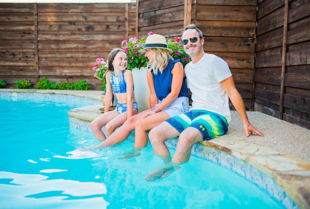 family dipping legs in pool shaded by horizontal wooden backyard privacy fence