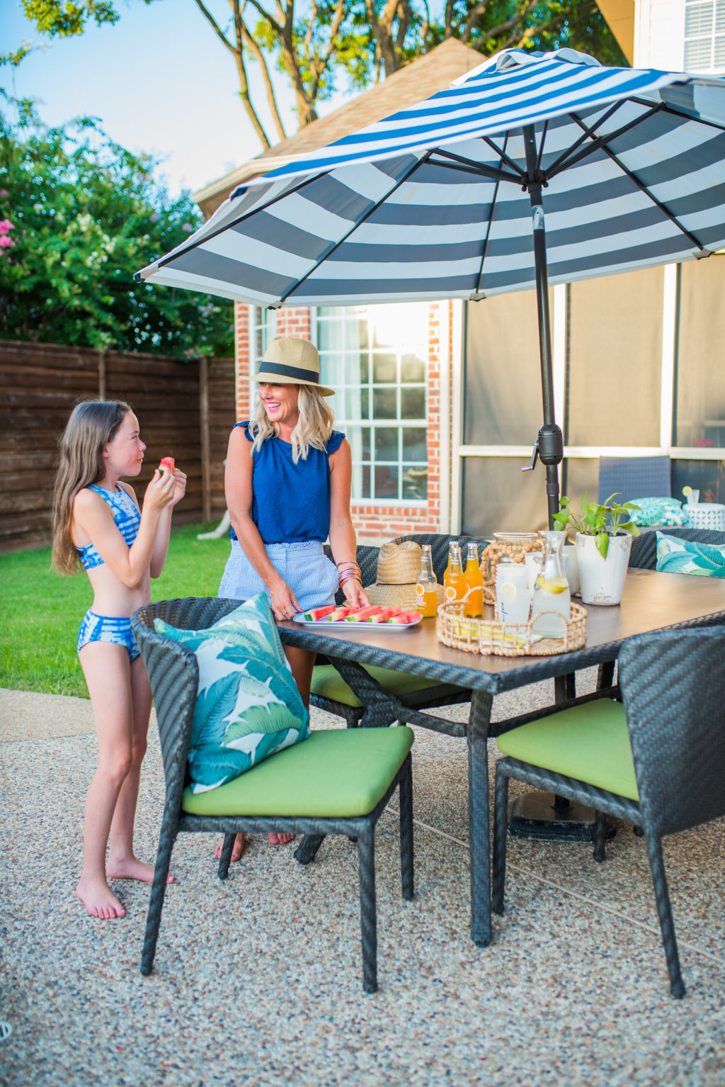 family eating watermelon on backyard patio behind wooden horizontal tall privacy fence