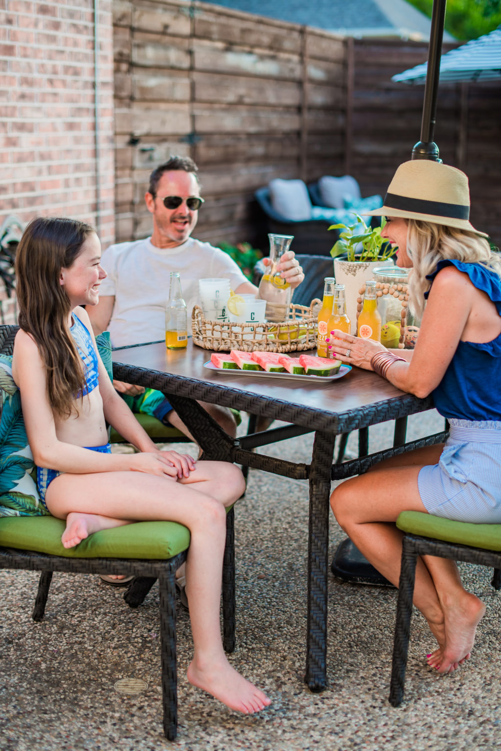 family eating watermelon on backyard patio furniture by pool