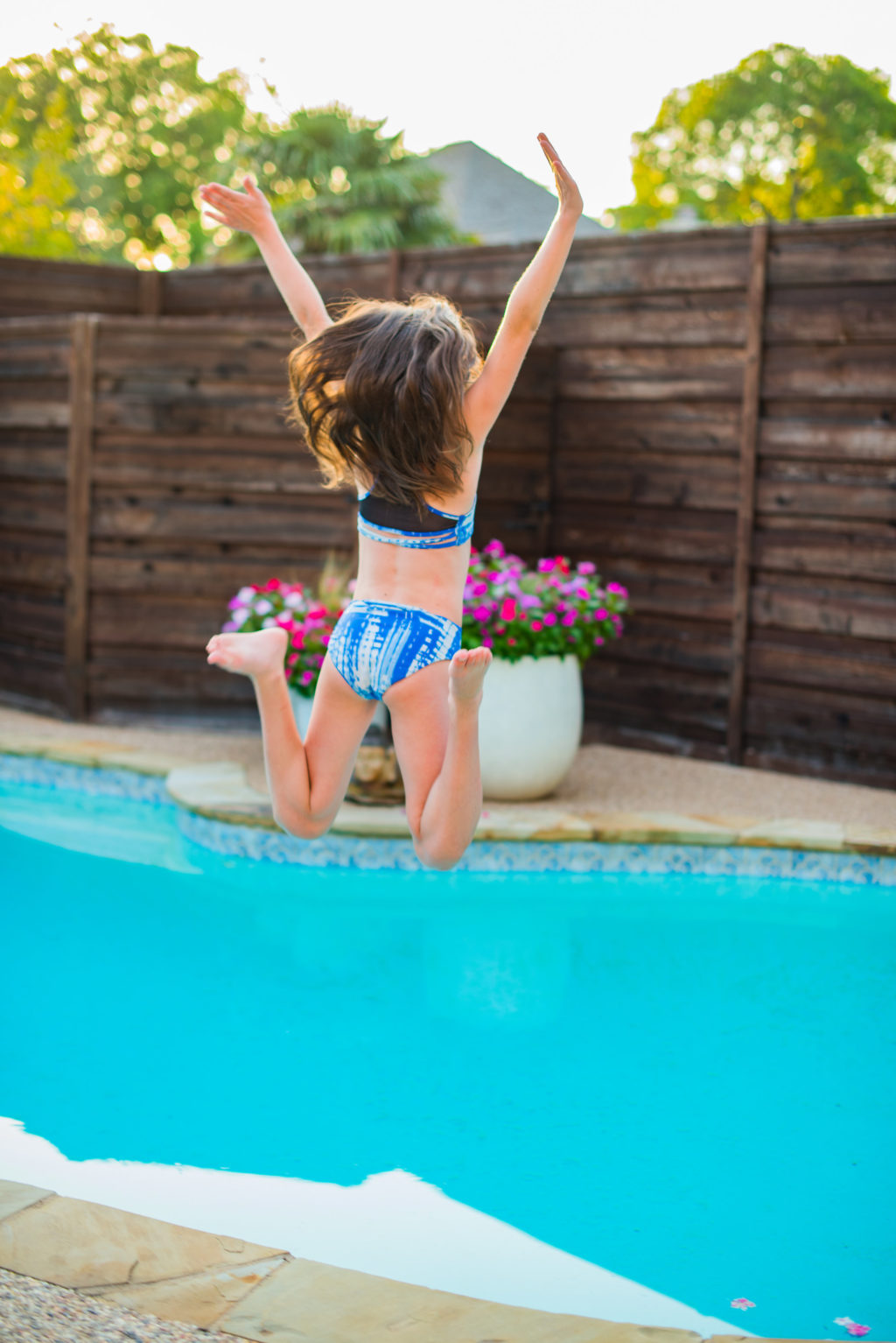kid jumping in pool behind backyard privacy fence during summer