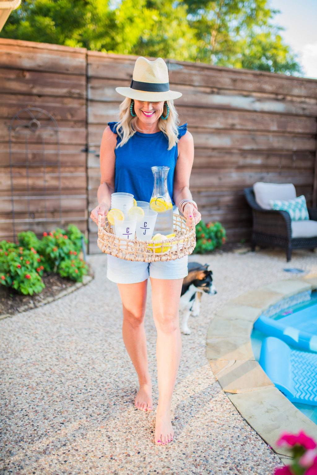 mom serving drinks by pool behind privacy fence in backyard