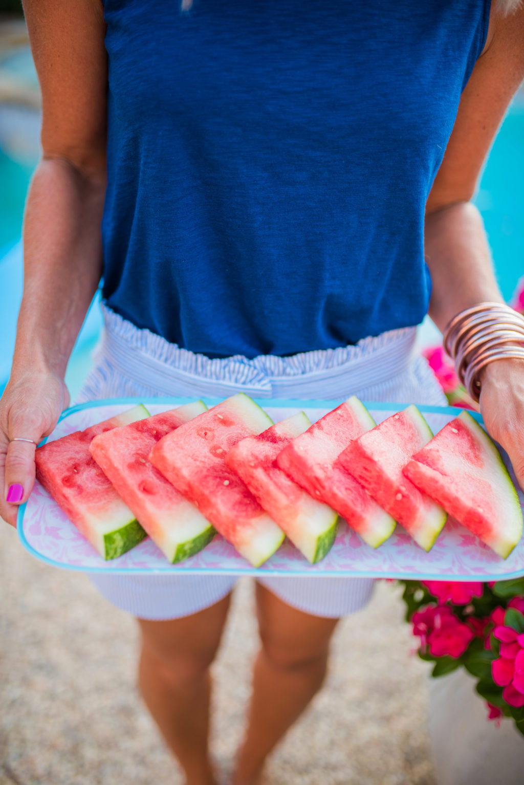serving watermelon wedges by the pool in summer