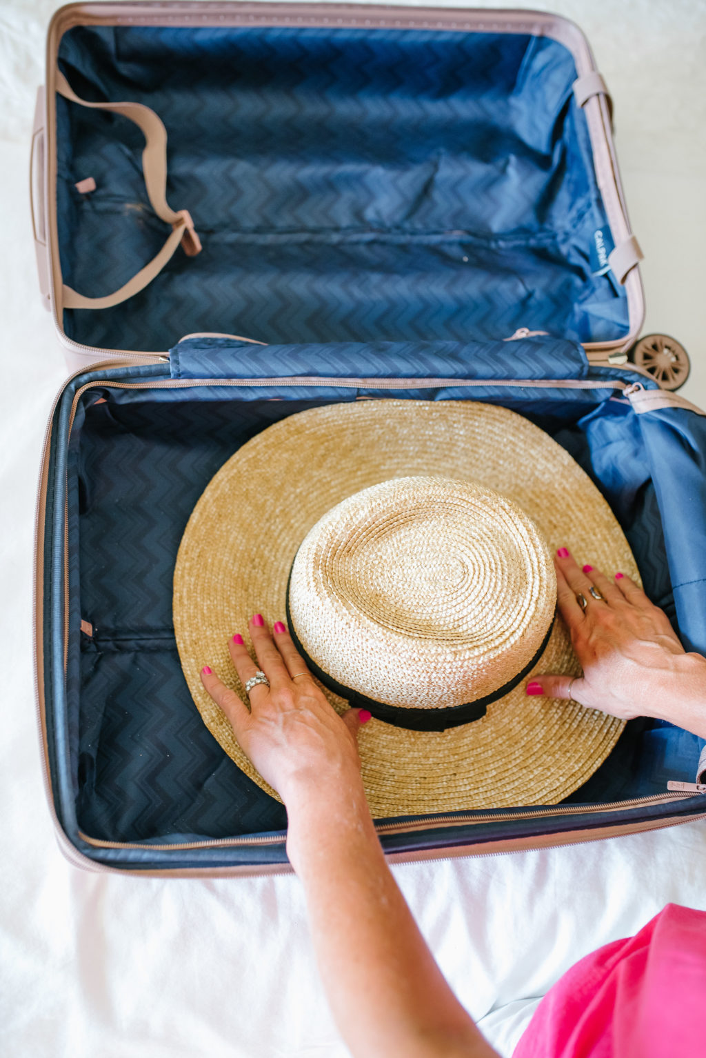 packing a hat on the bottom of a rolling carry on suitcase