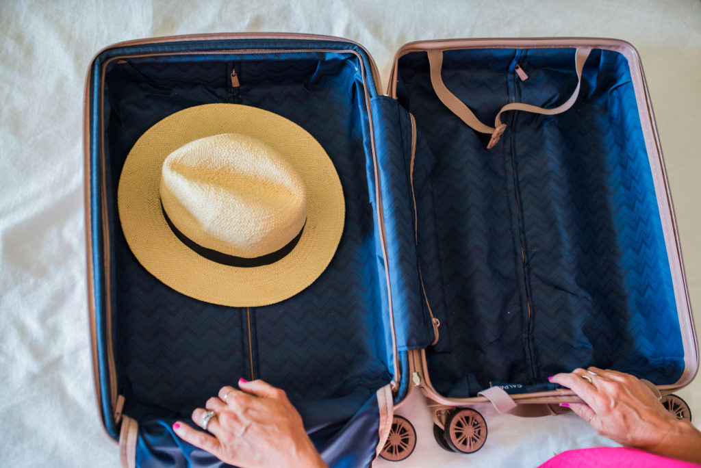 packing a hat in a suitcase on the bottom on the carry on luggage