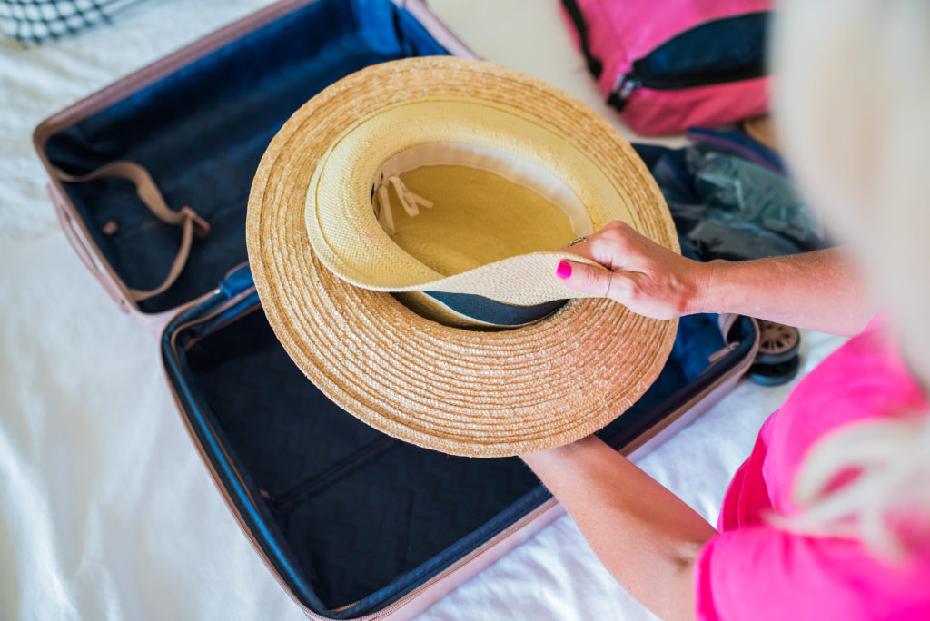 how to pack multiple hats in a suitcase by nesting one hat underneath the other
